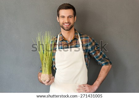 Gardening is my passion. Cheerful young gardener holding flower pot and smiling at camera while standing against grey background  - stock photo