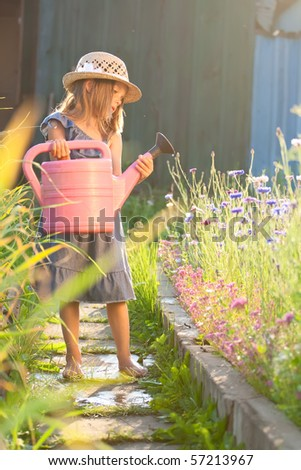 Gardening. Little beautiful girl pouring flowers from her watering can. - stock photo