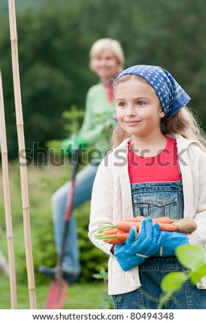 Gardening - little girl is working with mother in the vegetable garden - stock photo