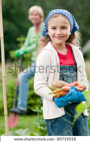 Gardening - little girl with mother working in vegetable garden - stock photo