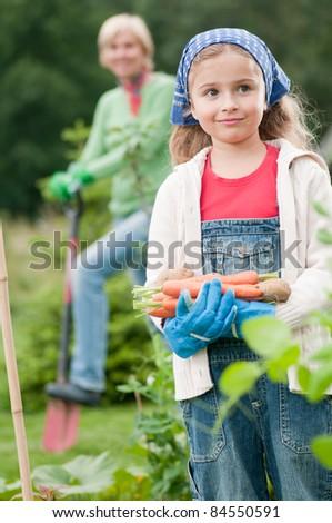 Gardening - little girl with mother working in vegetable garden - stock photo