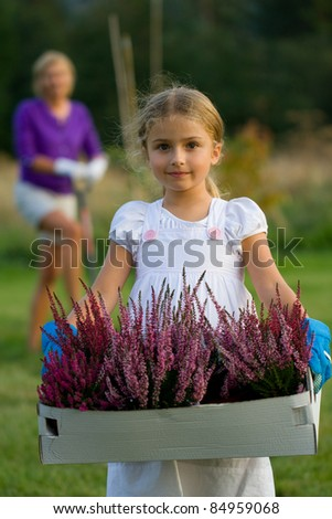 Gardening - little girl  working with mother in the  garden - stock photo