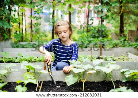 Gardening - little kid girl  working in vegetable garden - stock photo