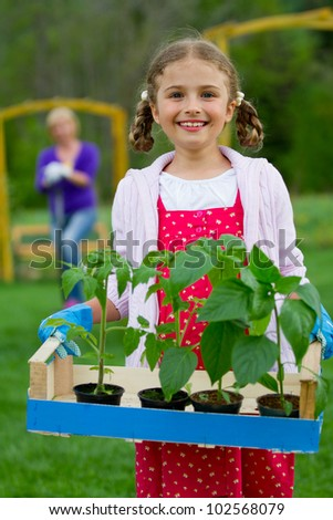 Gardening, planting concept - lovely girl working with mother in the garden - stock photo