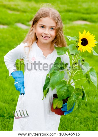 Gardening, planting concept - portrait of lovely girl with sunflower - stock photo