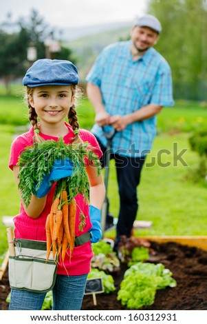 Gardening, planting, cultivation - lovely girl helping father in vegetable garden - stock photo