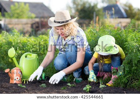 Gardening, planting - mother with daughter child plant strawberry seedlings into garden bed - stock photo