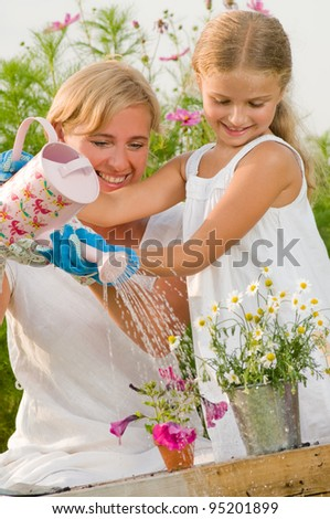 Gardening, planting - mother with daughter watering flowers in the flowerpot