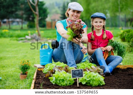 Gardening, planting - young girl with mother working in vegetable garden - stock photo