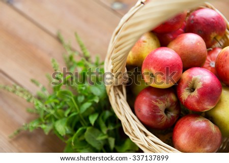 gardening, season, autumn and fruits concept - close up of wicker basket with ripe red apples and herbs on wooden table - stock photo