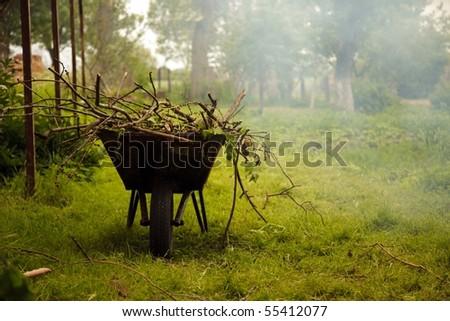 Gardening season - green lawn with wheelbarrow - stock photo