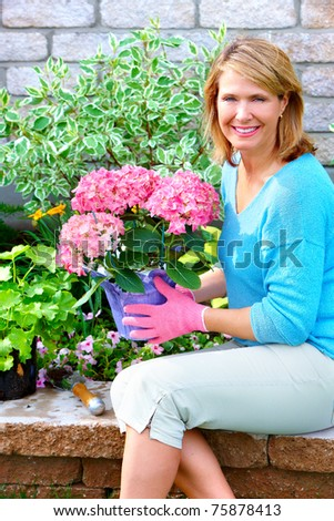 Gardening. Senior woman with flowers and plants.