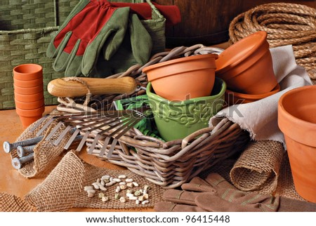 Gardening still life with flower pots, gardening tools, and planting supplies in wicker baskets with burlap and rope. - stock photo