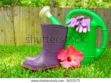 Gardening Supplies and Flower on Grass by Fence - stock photo