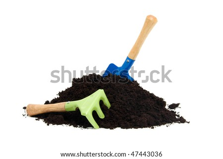 gardening tools and pile of garden soil over white background