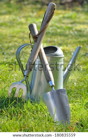 gardening tools and watering can on grass