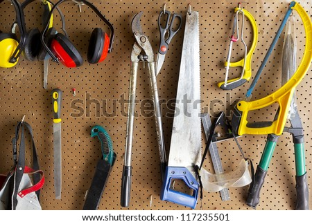 Gardening tools hanging off the wall - stock photo