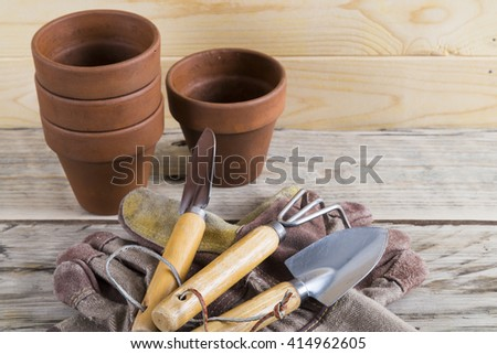 Gardening tools on gloves with pots - stock photo