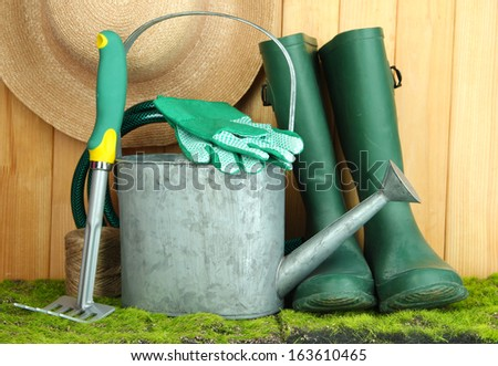 Gardening tools on grass on wooden background - stock photo
