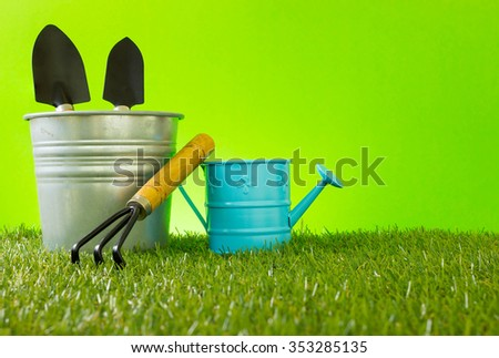 Gardening tools, watering can,  spade,rake and, shovel on green background