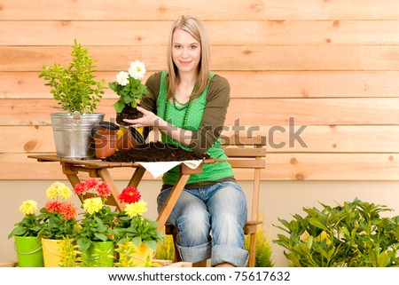 Gardening woman hold flowerpot plant spring terrace - stock photo