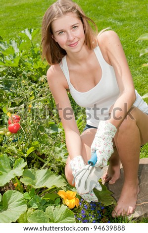 Gardening - young girl working in vegetable garden - stock photo