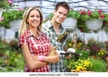 Gardening. Young smiling people florists working in the garden. .
