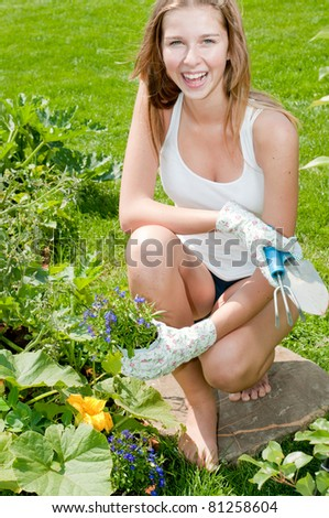 Gardening - young woman working vegetable garden - stock photo