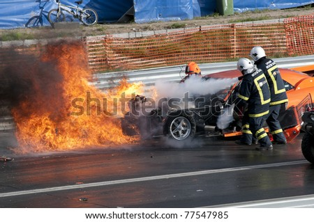 GARDERMOEN RACEWAY, NORWAY - MAY 14: Fire fighters try to control the fire after race car explodes into flames during a drag race on May 14,2011 at Gardermoen Raceway, Norway. - stock photo