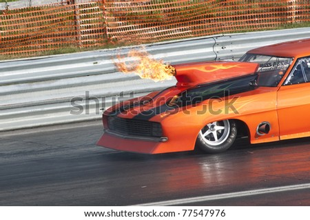 GARDERMOEN RACEWAY, NORWAY - MAY 14: Race car catches fire before it explodes into flames during a drag race on May 14,2011 at Gardermoen Raceway, Norway. - stock photo