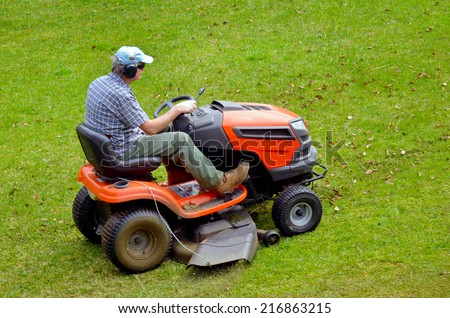 Gardner on ride-on lawn mower cutting grass. - stock photo