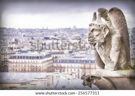 Gargoyle (chimera), famous stone demons, with Paris city on background. View from the tower of the Notre Dame de Paris cathedral. France. Travel, architecture concept. Copy space. Place for text. - stock photo