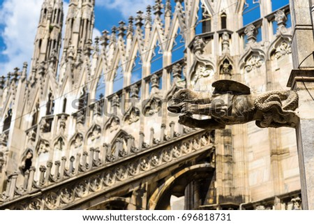 Gargoyle is on the roof of Milan Cathedral (Duomo di Milano) in Milan, Italy. Architectural background. Milan Cathedral is the largest church in Italy and the fifth in the world. Milan duomo exterior.