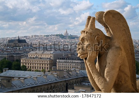 Gargoyle on Notre Dame Cathedral in Paris with Montmartre in the background