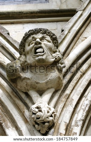 Gargoyle with hideous face and open mouth above the West Door of Salisbury Cathedral, Great Britain