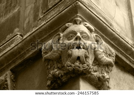 Gargoyle with protruding tongue. Architectural detail of old house in medieval town Arles (Provence, France). Aged photo. Sepia.