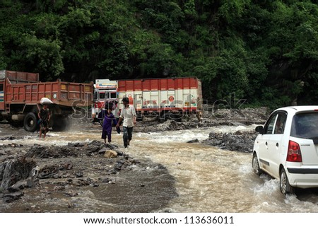 GARHWAL, INDIA - AUG 26 : Road traffic to Badrinath shrine are affected by flood water on August 26, 2012 in Garhwal, Uttrakhand, India. Landslides and rockfalls are often happening in this region.