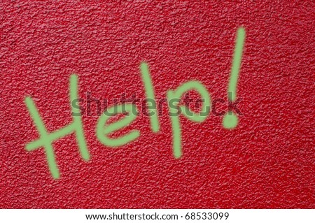 "Garish green airbrushed ""Help"" text on red painted stucco wall"