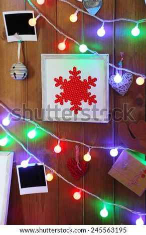 Garland, blank photo cards and pictures on wooden wall background - stock photo