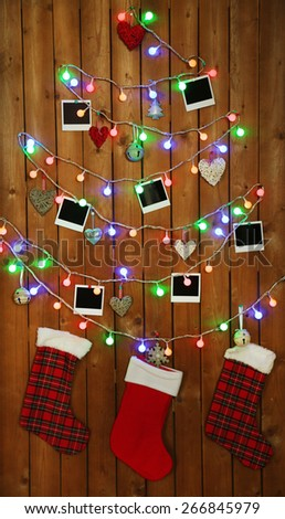 Garland in shape of Christmas tree with retro blank photos on wooden wall background - stock photo
