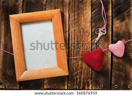 Garland knitting hearts, frame for a photo and key on old wooden panel. Background Valentines Day.Valentines day cards.