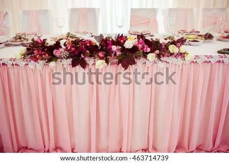 Garland made of dark flowers lies on pink tablecloth