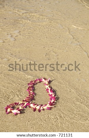 Garland of flowers on the beach - stock photo