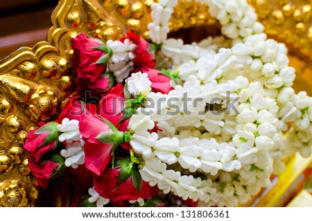 Garland of jasmine and rose flowers on golden tray