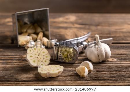 Garlic and garlic press on rustic wooden board - stock photo