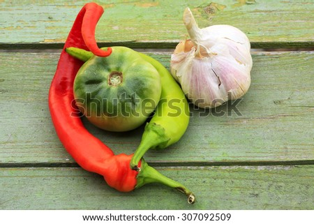 garlic and hot pepper green tomato on old wooden background - stock photo