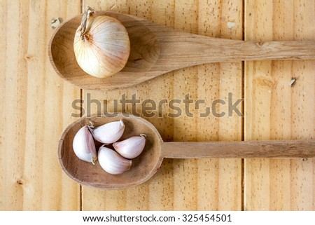 Garlic and onion on the wooden spoons