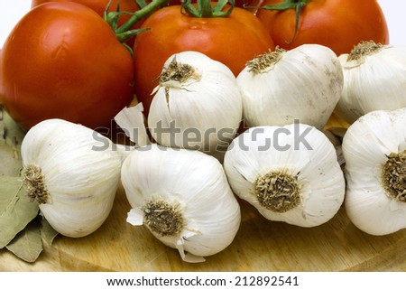 Garlic and red tomatoes on wooden board close up, Healthy vegetables, Photography