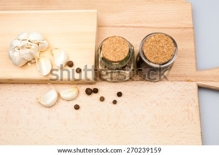 Garlic and spices on wooden kitchen board - stock photo