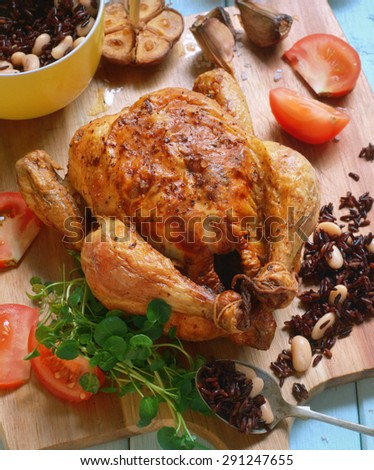 garlic and thyme roast chicken with black rice, beans and fresh tomatoes on garnish. selective focus